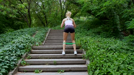 lift ups : Beautiful sexy athletic young blond woman runs upstairs, in the forest, park, in summer day. Performs exercises to strengthen the different muscles of the legs on the stairs.