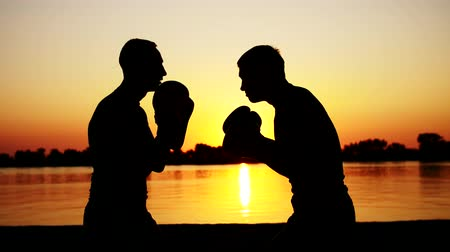 quimono : Two dark male figures, at sunrise, against the light, boxing, fighting in sparring, training in a pair of techniques of strikes. On sandy beach, in cargo port, near water, in summer