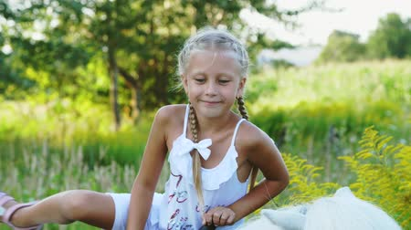 ranč : Blond girl of seven years, in a white dress, climbs, sits on a pony. Cheerful, happy family vacation. Outdoors, in the summer, near the forest Dostupné videozáznamy