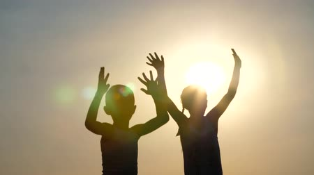 stín : Silhouettes, figures of children, boy and girl jumping, having fun, dancing, hugging against the background of the sun, at sunset in summer. Happy family. Slow motion