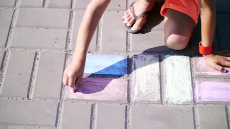 ayakkabı : close up, a girl in sunglasses, draw drawings with colored crayons on the asphalt, street tiles. A hot summer day. Stok Video