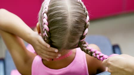 eski moda : Beautiful blond girl, of seven years old, braided two pigtails, do a hairstyle with pink locks of hair in a beauty salon, a hairdressers salon, in front of a large mirror. a little princess