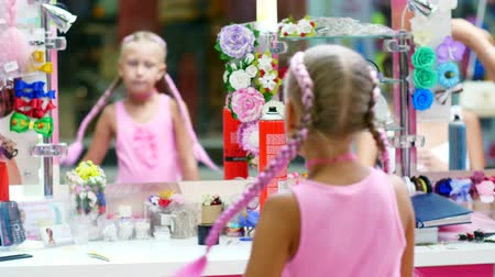 pigtailler : Beautiful blond girl, of seven years old, braided two pigtails, do a hairstyle with pink locks of hair in a beauty salon, a hairdressers salon, in front of a large mirror. a little princess