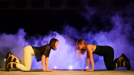 serra : Two athletic women, doing various fitness exercises with weighting on their legs, At night, in light smoke, fog, in light of multicolored searchlights, in an old abandoned hangar,