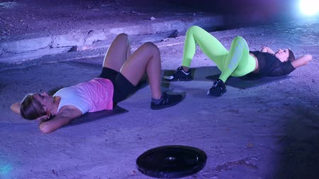 serra : Two athletic, sexy young women, doing fitness exercises in pair, At night, in light smoke, fog, in light of multicolored searchlights, in an old abandoned hangar, building Vídeos