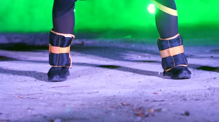 serra : close-up of two women legs with weightings on, doing fitness exercises , At night, in light smoke, fog, in light of multicolored searchlights, in an old abandoned hangar,