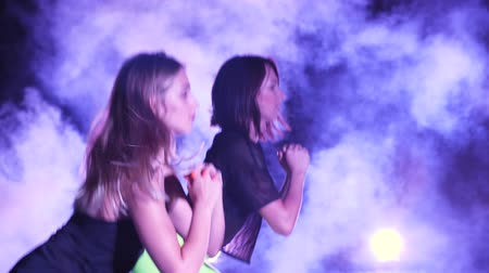 serra : Two athletic women, doing fitness exercises . At night, in light smoke, fog, in light of multicolored searchlights, in an old abandoned hangar,