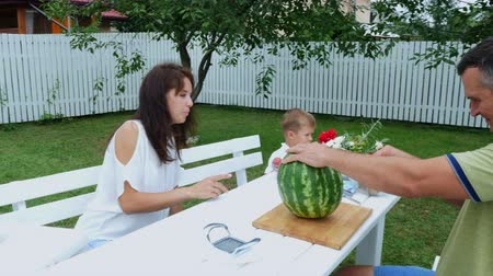наслаждаясь : A young family with two little funny children sitting at a dinner table in the garden, in summer. Dad cuts a large watermelon, is going to treat his family. lunch with the family. Стоковые видеозаписи