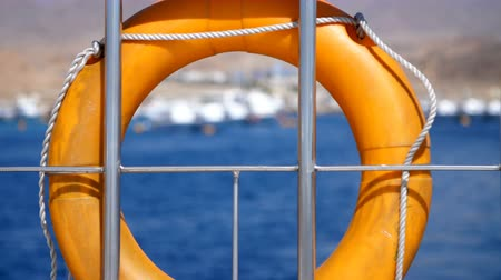 salva vidas : summer, sea, orange lifebuoy, hanging aboard a ferry, ship. special rescue equipment of the ship. saves the life of a person who is drowning.