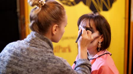 meksika : Halloween party, make-up artist draws a terrible makeup on the face of a brunette woman for a Halloween party. in the background, the scenery in the style of Halloween is seen