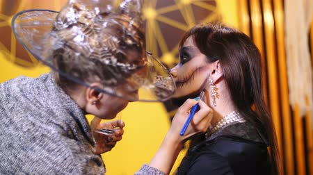 catrina : Halloween party, make-up artist draws a terrible makeup on the face of a brunette woman for a Halloween party. in the background, the scenery in the style of Halloween is seen