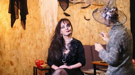 greasepaint : Halloween party, make-up artist draws a terrible makeup on the face of a brunette woman for a Halloween party. in the background, the scenery in the style of Halloween is seen