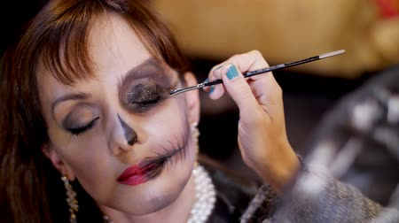 greasepaint : Halloween party, close-up, make-up artist draws a terrible makeup on the face of a brunette woman for a Halloween party. the scenery in the style of Halloween is seen Stock Footage