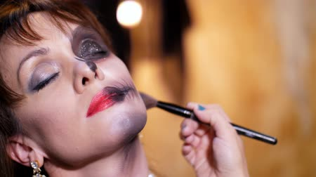 catrina : Halloween party, close-up, make-up artist draws a terrible makeup on the face of a brunette woman for a Halloween party. the scenery in the style of Halloween is seen Stock Footage