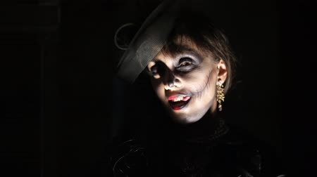 wampir : Halloween party, night, frightening portrait of a woman in the twilight, in the rays of light. woman with a terrible make-up in a black witch costume