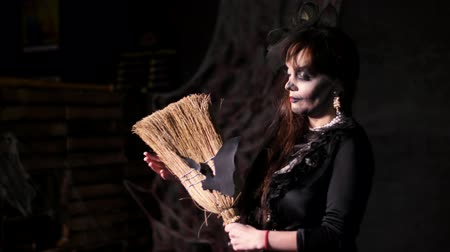 ведьма : Halloween party, night, frightening portrait of a woman in the twilight, in the rays of light. woman with a terrible make-up in a black witch costume. she holds a broom with a bat