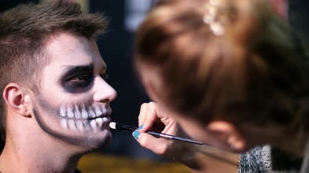 catrina : Halloween party, close-up, make-up artist draws a terrible makeup on the face of a man for a Halloween party. in the background the scenery in the style of Halloween is seen