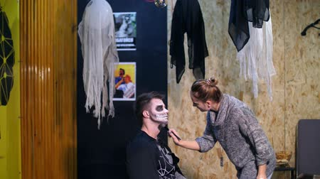 catrina : Halloween party, make-up artist draws a terrible makeup on the face of a man for a Halloween party. in the background, the scenery in the style of Halloween is seen