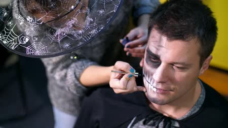 greasepaint : Halloween party, close-up, make-up artist draws a terrible makeup on the face of a man for a Halloween party. in the background the scenery in the style of Halloween is seen