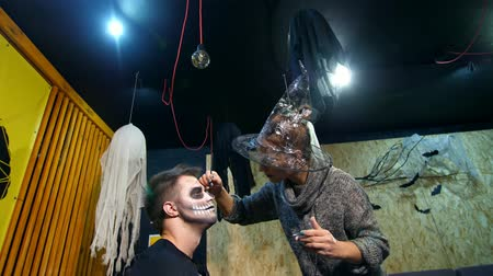 greasepaint : Halloween party, make-up artist draws a terrible makeup on the face of a man for a Halloween party. in the background, the scenery in the style of Halloween is seen
