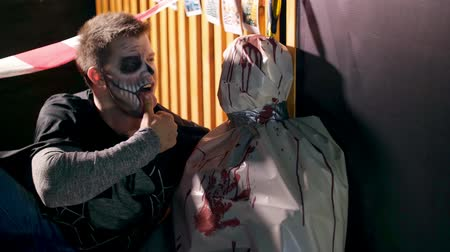 gruesome : Halloween party, night, twilight, in the rays of light, a man with a terrible makeup talking with a corpse wrapped in oilcloth, the corpse is smeared with blood. Stock Footage