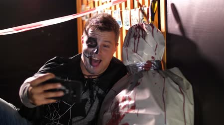 gruesome : Halloween party, night, twilight, in the rays of light, a man with a terrible makeup does selfie with a corpse wrapped in oilcloth, the corpse is smeared with blood.