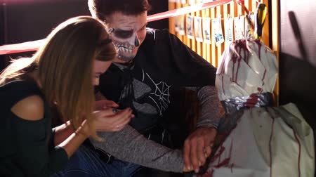 gruesome : Halloween party, night, twilight, in the rays of light, a man with a terrible makeup and a girl in a cat costume are making an indirect heart massage to a corpse wrapped in oilcloth, Stock Footage