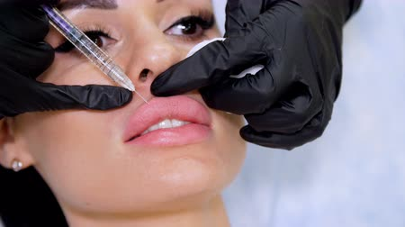 operacja plastyczna : medical office, doctor in black sterile gloves, injecting hyaluronic acid into the patient lips. Procedure for increasing the volume of lips, correction of lips shape.