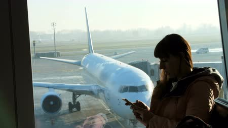 lounge : at the airport, in the waiting room, against the background of a window overlooking the airplanes and the runway, stands a young woman typing on the phone. see her silhouette Stock Footage