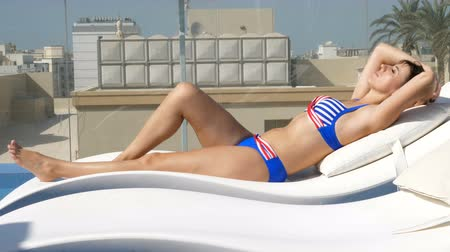 lefekvés : Woman in swimsuit relaxing at rooftop pool with city urban view . Young female model lying down at sun lounger Stock mozgókép