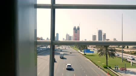 столбцы : DUBAI, UNITED ARAB EMIRATES, UAE - NOVEMBER 20, 2017: Traffic moves along a busy city road in afternoon. A view from Automatic walkway at Dubai Metro Station