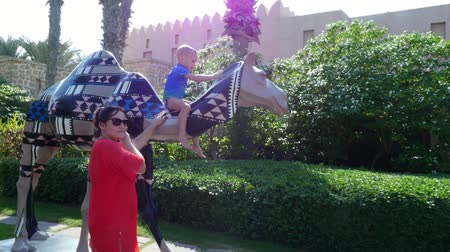 climbed : DUBAI, UNITED ARAB EMIRATES, UAE - NOVEMBER 20, 2017: Hotel Jumeirah Al Qasr Madinat , mom and son walking around hotel. child climbed onto colored statue of a camel.