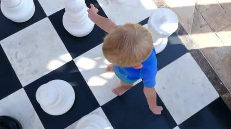 шах и мат : DUBAI, UNITED ARAB EMIRATES, UAE - NOVEMBER 20, 2017: Hotel Jumeirah Al Qasr Madinat , baby boy playing big outdoors chess on a large chessboard