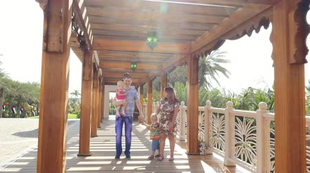 vazo : DUBAI, UNITED ARAB EMIRATES, UAE - NOVEMBER 20, 2017: Hotel Jumeirah Al Qasr Madinat, family walk along a wooden gazebo, decorated with lanterns in Arabic style Stok Video