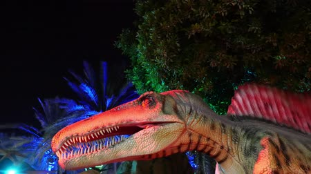 temas animais : DUBAI, UNITED ARAB EMIRATES, UAE - NOVEMBER 20, 2017: Dinosaur Park at Dubai Garden Glow park, illuminated at night. a lot of different dinosaurs, look alive