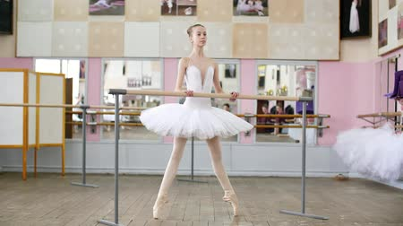 dansçılar : in the ballet hall, girl in white pack is engaged at the ballet, rehearse Roleve, goes up on toes, in pointe shoes , Young ballerina standing at railing in ballet hall. Stok Video
