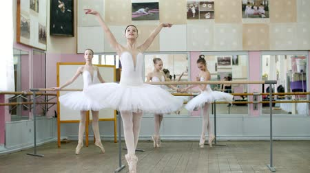 bale : in ballet hall, girls in white ballet skirts are engaged at ballet, rehearse turning, Young ballerinas standing on toes in pointe shoes elegantly, at railing in ballet hall. Stok Video