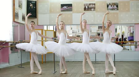 baletnica : in ballet hall, girls in white ballet skirts are engaged at ballet, rehearse tendue forward battement, Young ballerinas standing in pointe shoes, at railing in ballet hall.
