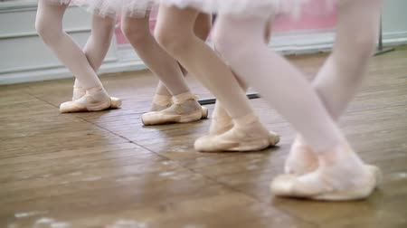 колготки : in ballet hall, Young ballerinas perform pas echappe in pointe shoes, goes up on toes, close-up