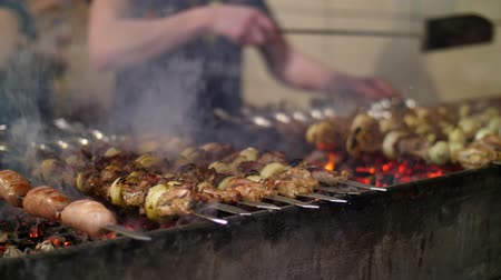 kabab : Grilled kebab cooking on metal skewer closeup. Roasted meat cooked at barbecue. BBQ fresh beef meat chop slices. Traditional eastern dish, shish kebab. Grill on charcoal and flame, picnic, street food Stock Footage
