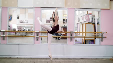 колготки : in dancing hall, Young ballerina in purple leotard performs developpe attitude on pointe shoes, raises her leg up behind elegantly, standing near barre at mirror in ballet class.