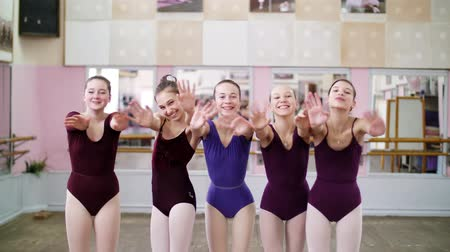 taniec towarzyski : in dancing hall, Young girls ballerinas in purple leotards hug, smile, wonderful ballet school students, blowing kisses Wideo