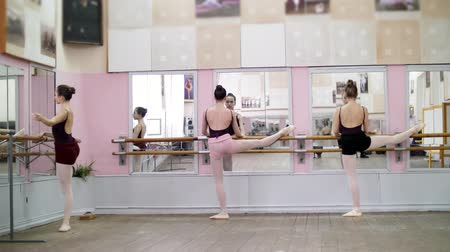 baletnica : in dancing hall, Young ballerinas in black leotards stretching at barre, on pointe shoes, elegantly, standing near barre at mirror in ballet class.