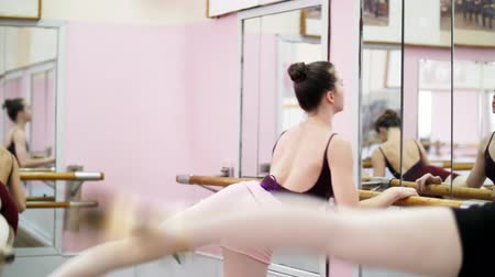 колготки : in dancing hall, Young ballerinas in black leotards perform grand battement back at barre, elegantly, standing near barre at mirror in ballet class.