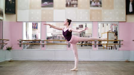 колготки : in dancing hall, Young ballerina in black leotard performs 1 arabesque, raises her leg up behind elegantly, standing near mirror in ballet class.