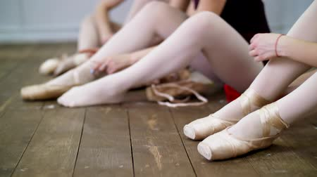 dançarina : close up, ballerinas change their shoes into special ballet shoes, pointe shoes, lace with ballet ribbons, on an old wooden floor, in ballet class.