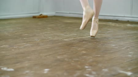 колготки : close up, in dancing hall, ballerina perform ssissonne simples , She is standing on toes in pointe shoes elegantly , on an old wooden floor, in ballet class.