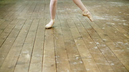 колготки : close up, in dancing hall, ballerina perform step pointe , She is standing on toes in pointe shoes elegantly , on an old wooden floor, in ballet class.