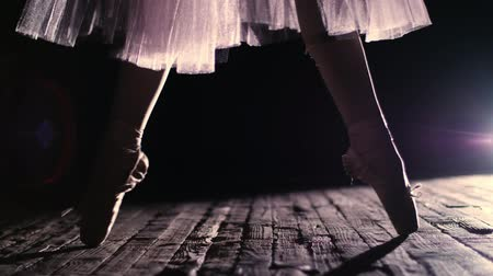 колготки : close up, in rays of spotlight, on the stage of the old theater hall. ballerina in white ballet skirt, raises on toes in pointe shoes, performs elegantly a certain ballet exercise, relleve Стоковые видеозаписи