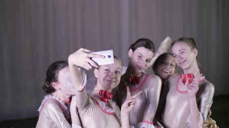 gracefully : young girls ballerinas make selfies during a break in ballet rehearsal, on the stage of the old theater hall. Stock Footage